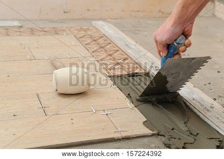 Worker instals tiles on the floor. He put glue using comb trowel.