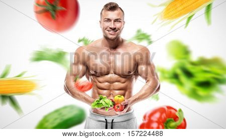 Shaped and healthy bodybuilder holding a fresh vegetables shaped abdominal isolated on white background colored retouched