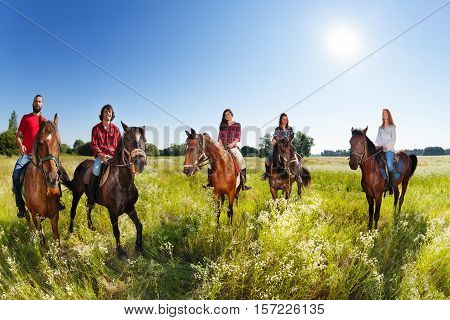 Group of five young people enjoy riding horses in flowery meadows