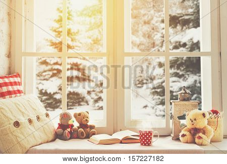 Christmas winter window with a book a cup of hot tea and a teddy bear
