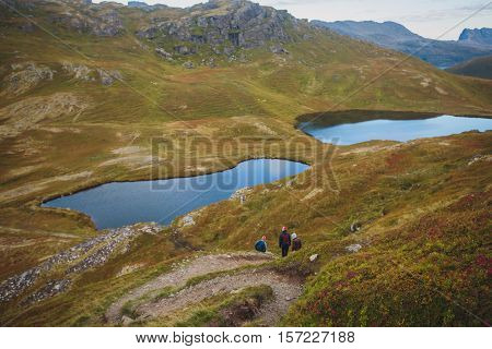 Beautiful Vibrant Norwegian Mountain Landscape from Ryten peak - famous mountain in Lofoten Islands, Moskenes municipality, Nordland with a view of Kvalvika beach, with hiking tourists and blue sky poster