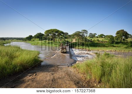 road in the wilderness crossing river in natural park, safari trip in Tanzania, Africa