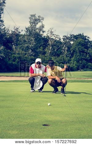 Golfer and caddy contemplating putting shot. Toned image