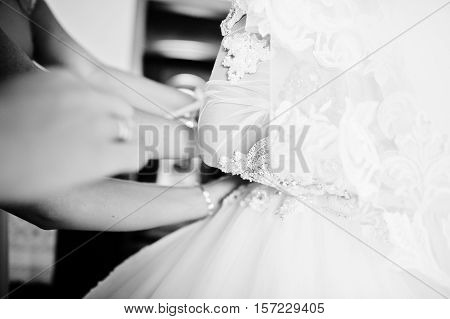 Hand of bridesmaid who dressed the dress on bride. Black and white photo