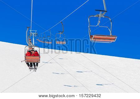 Chairlifts transport skiers couple and snowboarders up a snowy at a winter ski resort in the Alps white snow and blue sunny sky background