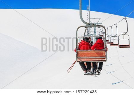 Skiers couple in red skisuits go on a ski lift at chairlift ropeway against snowy mountains landscape of ski slopes and blue sky - winter holidays concept