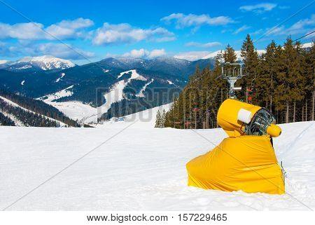 Yellow snow maker machine (snow gun snow cannon) at ski slopes resort - standard equipment device for making snow to create better skiing conditions or to extend the skiing season