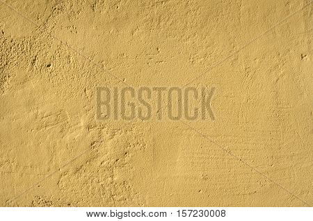 Ocher house rough plastered facade wall closeup as background