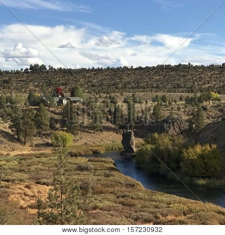 A pillar of rock standing straight and tall in the Deschutes River as it winds through a canyon in Central Oregon on a sunny fall day.