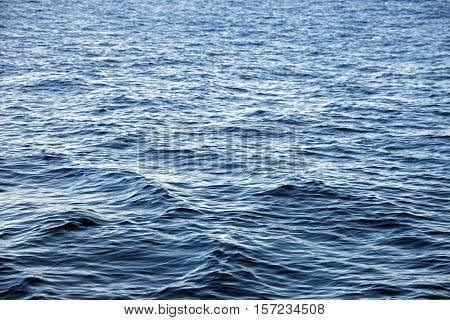 Background of transparent crystal blue sea water surface ripple with sun reflection in summer. Water background. Ocean water texture.