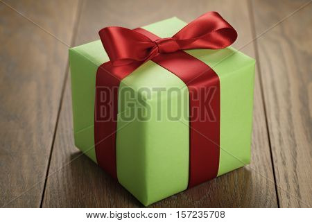simple green paper gift box with red ribbon bow on oak table, shallow focus