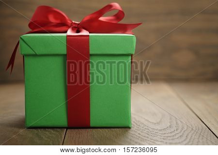 green paper gift box gift box with lid and red ribbon bow on wood table with copy space, shallow focus