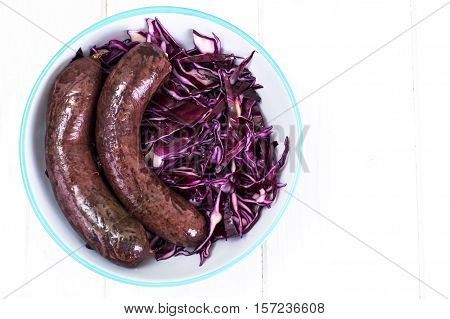 Blood sausage with garnish on old wooden table. Studio Photo