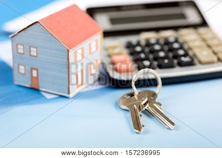 The concept of home ownership  with house and keys and calculator studio shoot