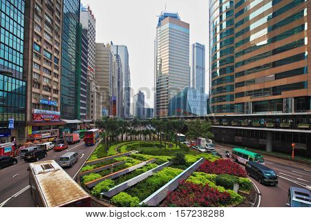 HONG KONG - DECEMBER 11, 2014: Hong Kong Special Administrative Region. Fancy driving roundabout with colorful flower beds. Modern skyscrapers and narrow streets between them