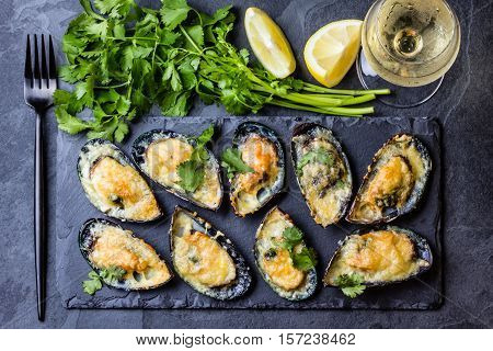 Seafood. Shellfish mussels. Baked mussels with cheese, cilantro and lemon in shells on slate stone board. Plate of mussels, cold white wine, lemon and cilantro on black stone background. Top view