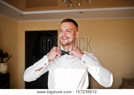 Man Wearing Bow Tie On Shirt. Gathering Of Groom On Wedding Day.
