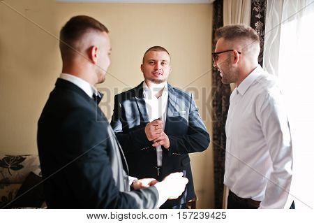Three Handsome Male Friends Meet And Speeking Each Other. Groomsman Or Best Man Greeting Groom At We