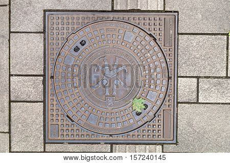Manhole cover on pavement with patterns, Dusseldorf, Germany