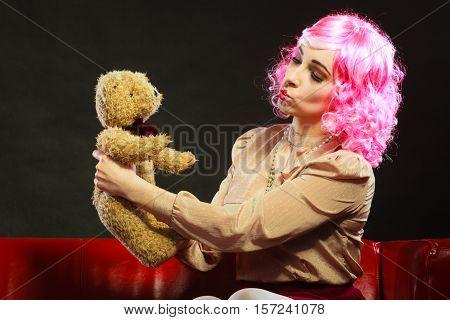 Mental disorder concept. Young childlike woman like puppet doll sitting with teddy bear toy on red couch dark black background