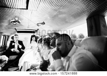 Stylish Groomsman Or Bes Man Of Groom And Bridesmaids With Wedding Couple Inside Limousine At Weddin