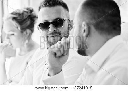 Stylish man on sunglasses speaking with friend. Groomsman at wedding. Black and white photo