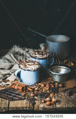 Hot chocolate in mugs with whipped cream and cinnamon, anise, nuts and cocoa powder on rustic wooden background, selective focus, copy space, vertical composition