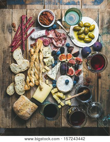 Wine and snack set with various wines in glasses, meat variety, bread, sun-dried tomatoes, honey, green olives, figs, nuts and fresh berries on wax paper over rustic wooden table background, top view