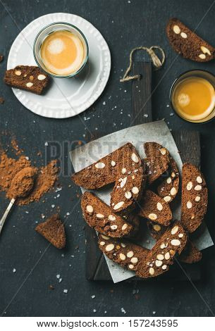 Dark chocolate and sea salt Biscotti cookies with almonds and two glasses of coffee espresso on wooden serving board over dark stone background, top view, selective focus, vertical composition