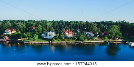 Beautiful super wide-angle aerial view of Stockholm archipelago skerries and suburbs with classic sweden scandinavian designed cottage houses from massive ferryboat