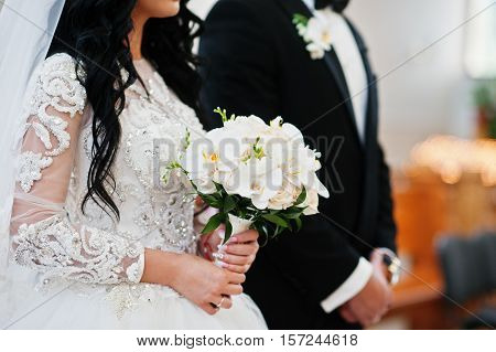 Wedding Bouquet Of White Orchids On Hand Of Bride On Church Ceremony.