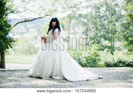 Gorgeous Curly Brunette Bride With Wedding Bouquet On Hands Posed On Park.