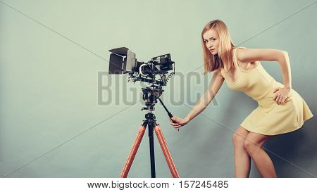 Photographer girl shooting images. Attractive fashionable blonde woman taking photos with camera blue background