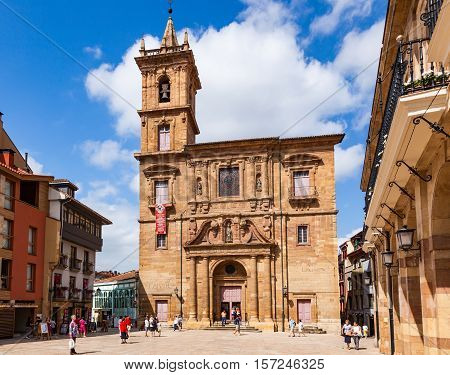 OVIEDO SPAIN - AUGUST 14 2013: Tourists and local residents stoll on the Plaza Nueva square with the San Isidoro church.