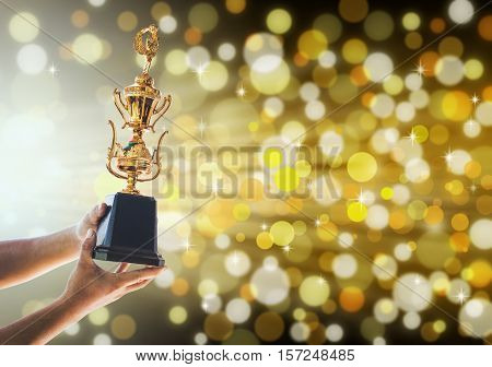 Win concept,Man holding up a gold trophy cup is winner in a competition with gold background.