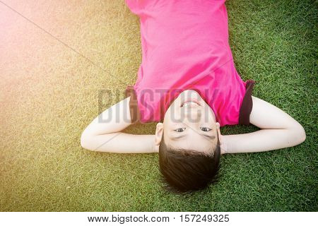 Little Asian child laying down on the grass with sun light