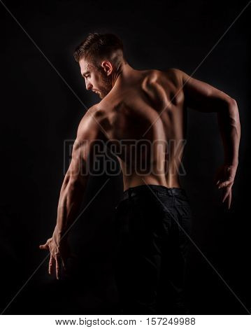 Bodybuilder posing on a black background. Dramatic portrait of an athlete. Drying. Relief and sculptural muscles of the body. Concept of healthy lifestyle. The muscles of the back and shoulders.