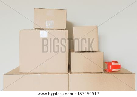 Variety of Packed Moving Boxes and Tape Gun In Empty Room Against Wall.