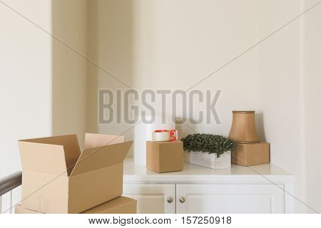 Variety of Packed Moving Boxes and Materials In Empty Room.