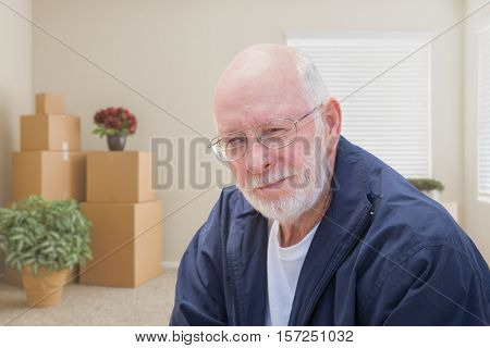 Senior Man in Empty Room with Packed Moving Boxes.