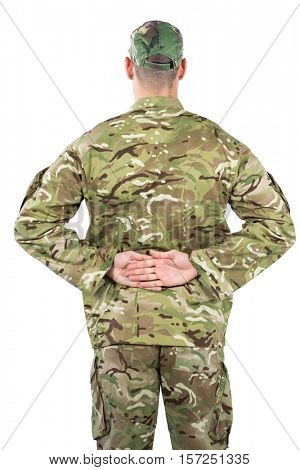 Rear view of soldier standing against white background with his hands behind back