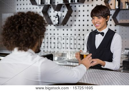 Barmaid serving drink to man at bar counter in bar