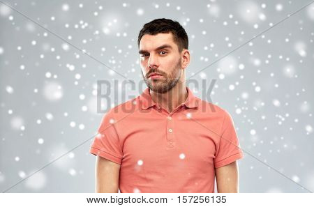 doubt, expression, winter, christmas and people concept - suspicious man thinking over snow on gray background
