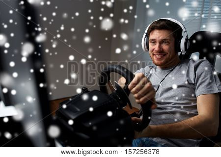 technology, gaming, entertainment and people concept - happy smiling young man in headphones with pc computer playing car racing video game at home and steering wheel over snow