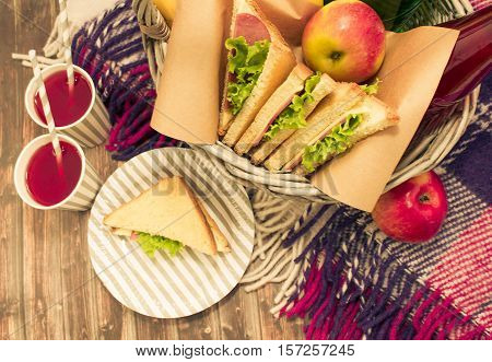 A picnic with lemonade,picnic basket, sandwiches, bananas, apples, plaid
