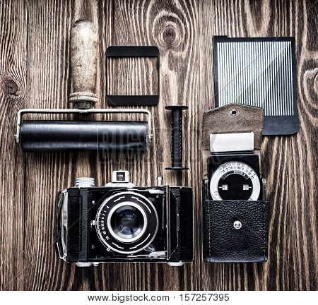 vintage camera, exposure meter and another trappings of film photography. photographer's desk