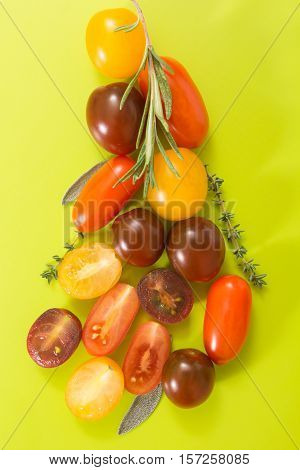 Colorful Cherry Tomatoes Cluster With Herbs, On Chartreuse Yellow Background.