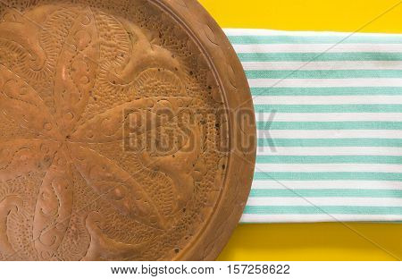 Old oriental copper dish on blue striped folded towel and yellow background.