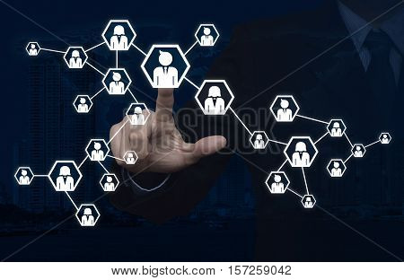 Businessman pressing network icon over world map and city tower Communication business concept Elements of this image furnished by NASA