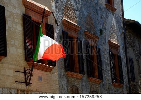 Italian flag fluttering on wind and windows with brown window shutters